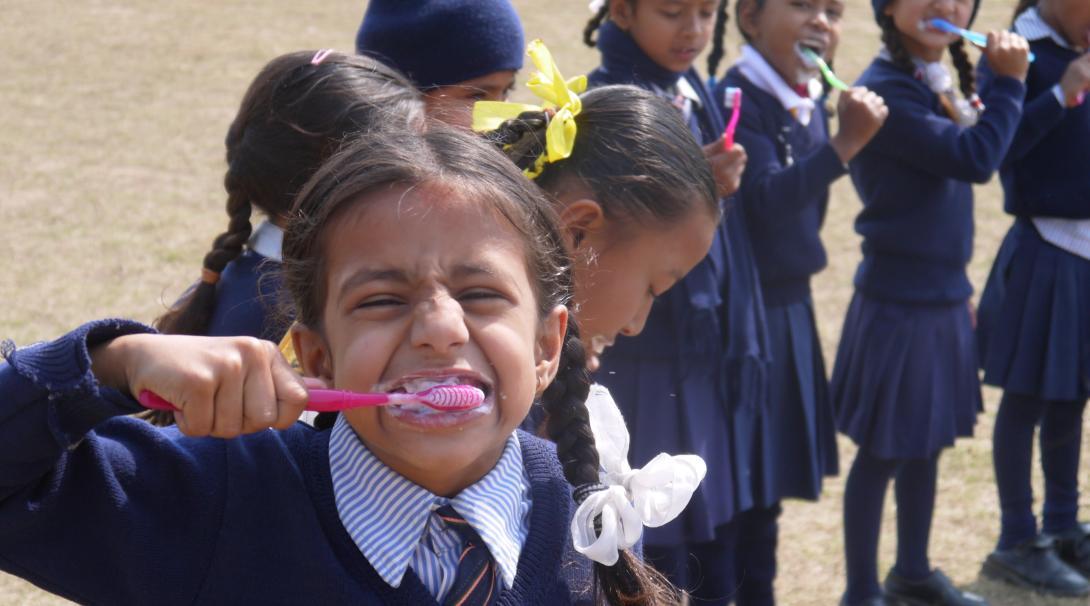 Una niña pequeña lavándose los dientes durante un taller de higiene en Nepal.